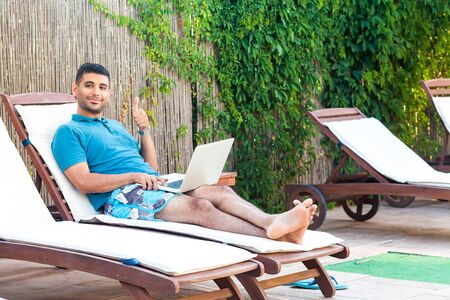 Portrait of positive handsome bearded young adult freelancer man in blue t-shirt and shorts lying on cozy sunbed with laptop on poolside, showing thumbs up and lookingat camera. Lifestyle concept Stok Fotoğraf