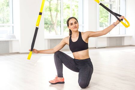 Portrait of happy beautiful young sports woman is doing TRX training, sitting on the floor and holding fitness straps while taking break. Wotkout in gym, looking at camera, indoor, window background