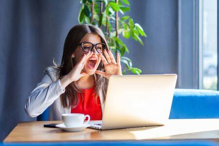 Portrait of angry brunette young woman in glasses sitting, looking at her laptop screen on video call and screaming to share something important. indoor studio shot, cafe, office background.