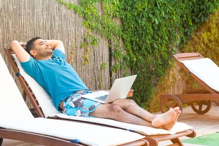 Portrait of pleasure bearded young adult freelancer man in blue t-shirt and shorts lying on cozy sunbed with laptop and vizualization his dream. Lifestyle concept, outdoor, summer vacation, open air