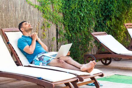 Portrait of pleading handsome bearded young adult prayer man in blue t-shirt and shorts lying on cozy sunbed with laptop on poolside and pleased to help him god. Lifestyle, outdoor, summer vacation Фото со стока