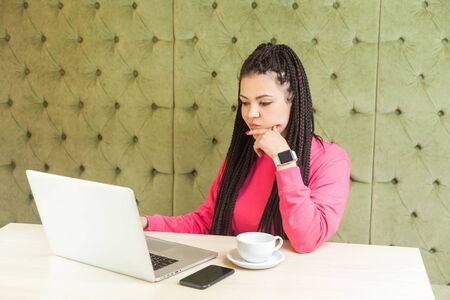 Beautiful thoughtful young freelancer with black dreadlocks in pink blouse is sitting in cafe and working on laptop, wait for new idea and planning own strategy, holding one hand on chin and thinking. Фото со стока