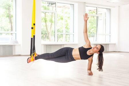 Portrait of young attractive muscular woman in black top and leggings standing on perfect side plank position use fitness straps, doing push ups while legs hanging on trx. Indoor, window background