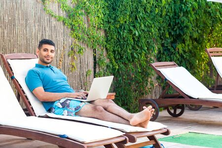 Portrait of happy handsome bearded young adult freelancer man in blue t-shirt and shorts lying on deck chair with laptop on poolside and looking at camera. Lifestyle concept, outdoor, summer vacation