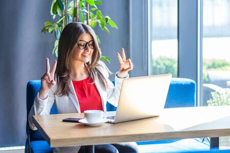 Portrait of happy beautiful stylish brunette young woman in glasses sitting, looking at her laptop monitor on video call with victory peace sign. indoor studio shot, cafe, office background.