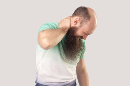 Neck pain. Portrait of sick middle aged bald man with long beard in light green t-shirt standing and holding his painful neck. indoor studio shot, isolated on grey background.