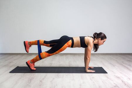 Side view portrait of young muscular woman wearing black top and orange leggings standing on plank position use fitness gum. Strong girl fitness exercising with expander. Indoor, white wall background