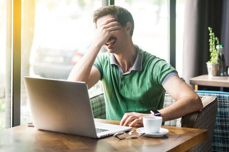 I don't want to look at this. Young scared or shy businessman in green t-shirt sitting and working on laptop, covering his eyes. business and freelancing concept. indoor shot near window at daytime. Banco de Imagens