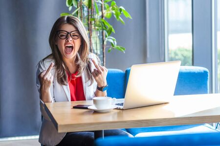 Portrait of aggressive brunette young woman in glasses sitting, looking at camera and showing middle finger fuck sign and screaming with angry face. indoor studio shot, cafe, office background.