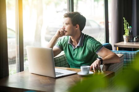 Young thoughtful businessman in green t-shirt sitting and working on laptop, looking to outside and thinking about his plans. business and freelancing concept. indoor shot near big window at daytime. Фото со стока