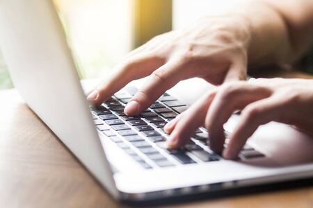CLoseup of human hand typing on laptop keyboard. Young businessman sitting and working on laptop. business and freelancing concept. indoor shot near window at daytime.