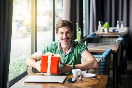 Young happy businessman in green t-shirt sitting and holding big red gift box and looking at camera with toothy smile. business and freelancing concept. indoor shot near big window at daytime. Banco de Imagens