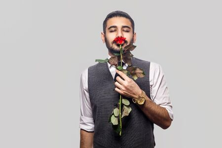 Portrait of handsome bearded brunette man in white shirt and waistcoat standing, holding red rose flower, smelling and enjoying with closed eyes. indoor studio shot isolated on gray background. Stok Fotoğraf