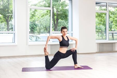 Full lenght portrait of young adult sporty attractive woman in black pants and top is doing horse rider exercise, anjaneyasana pose, working out, indoor, yoga studio, looking at camera, window background Stock fotó