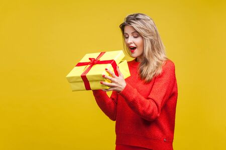 Portrait of surprised beautiful blonde woman with red lipstick in bright casual sweater, looking inside gift box with amazement, unboxing present. indoor studio shot isolated on yellow background
