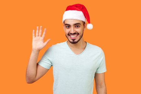 Hello! Portrait of positive handsome bearded man in santa hat and casual white t-shirt waving raised hand and saying hi to camera, christmas time. indoor studio shot isolated on orange background Banco de Imagens