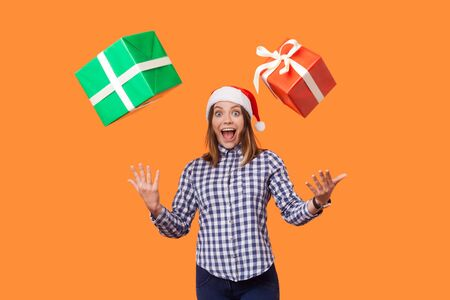 Portrait of amazed brunette woman in santa hat and checkered shirt standing with open mouth and raised hands, trying to catch flying christmas gifts. indoor studio shot isolated on orange background