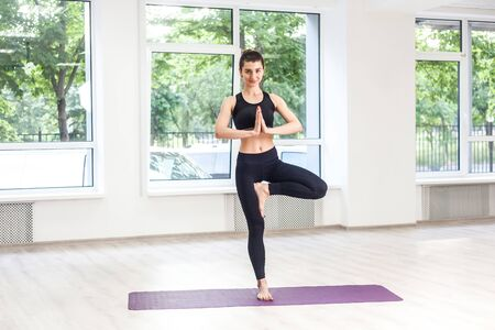 Full lenght portrait of young adult sporty attractive woman in black pants and top is practicing yoga, doing balance exercise, tree pose and vrksasana, indoor, studio shot, looking at camera