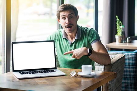 Young shocked businessman in green t-shirt sitting, pointing and showing laptop display. surprised face and looking at camera. business and freelancing concept. indoor shot near big window at daytime. 스톡 콘텐츠