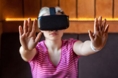 Portrait of serious young adult woman in pink t-shirt sitting in cafe, wearing virtual reality headset and watching video, playing game on simulator raised arms showing stop sign, looking at camera,