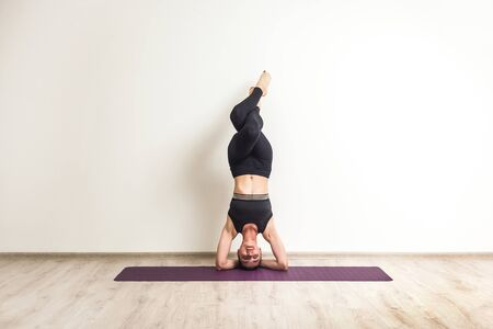 Full length portrait of sporty attractive young adult fit woman doing sports training, supported headstand posture, salamba sirsasana with crossed legs, indoor, studio shot on white background Foto de archivo