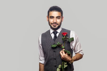 Portrait of handsome bearded brunette man in white shirt and waistcoat standing, holding rose red flower and looking at camera with smile. indoor studio shot isolated on gray background.