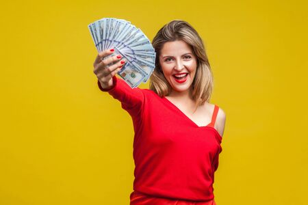 Portrait of excited rich beautiful woman in red dress standing showing dollar bills to camera, looking with open mouth, boasting salary or lottery win. indoor studio shot isolated on yellow background Imagens