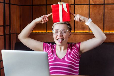 Childish happy young woman with short hair in pink t-shirt and eyeglasses is sitting in cafe, holding red present box on head,pointing finger to gift looking at camera and showing tongue out. Indoor