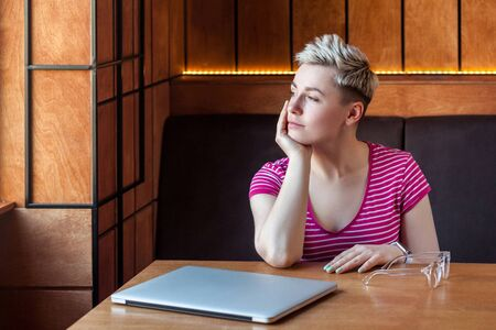 Portrait of thoughtful beautiful young bussineswoman with blonde short hair in pink t-shirt is sitting in cafe, finishing work and looking away, relaxing and smile. Indoor, healthy lifestyle Banque d'images - 131854488