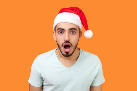 Portrait of surprised bearded young man in santa claus hat and casual white t-shirt standing with open mouth, looking serious and shocked at camera. indoor studio shot isolated on orange background