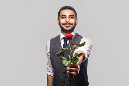 Portrait of funny handsome bearded brunette man in white shirt and waistcoat standing, holding and giving rose red flower and smiling at camera . indoor studio shot isolated on gray background. Stok Fotoğraf
