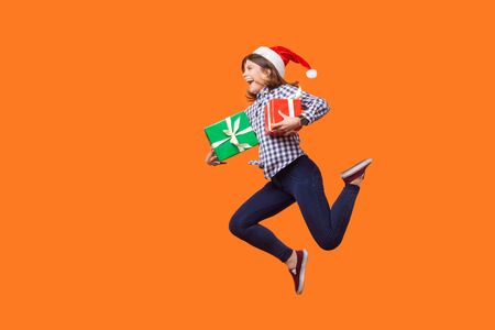 Side view portrait of extremely joyous brunette woman in santa hat jumping or running in air with wrapped xmas gift boxes, celebrating discounts. indoor studio shot isolated on orange background