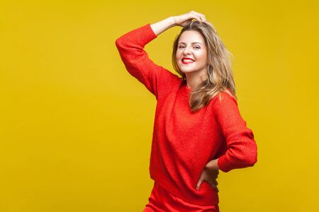 Portrait of sensual happy blonde woman with red lipstick in casual sweater standing, touching hair with hand and looking at camera, fashion model. indoor studio shot isolated on yellow background