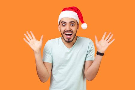 Portrait of amazed happy bearded young man in santa claus hat and casual white t-shirt standing with open mouth and raised hands, excited and shocked. indoor studio shot isolated on orange background 스톡 콘텐츠