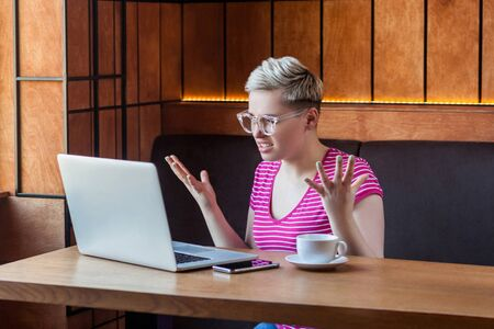 Aggressive unhappy young girl freelancer with blonde short hair, in pink t-shirt and eyeglasses is sitting in cafe and having bad mood are admonishing a worker through a webcam with raised arms. Stok Fotoğraf