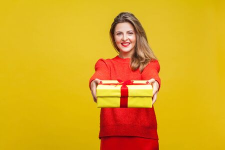 For you! Portrait of happy beautiful blonde woman with red lipstick in bright casual sweater, giving wrapped gift box to camera, christmas present. indoor studio shot isolated on yellow background