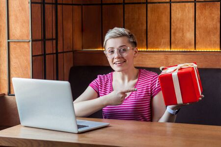 Portrait of beautiful happy young woman with short hair in pink t-shirt is sitting in cafe, pointing finger to red present box, easy to order online buy, looking at camera with toothy smile. Indoor