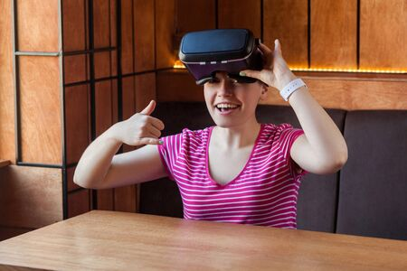 Like it! Portrait of positive young woman in pink t-shirt sitting and holding virtual reality headset and showing thumbs up with cheerful face, looking at camera and toothy smile. Indoor, lifestyle