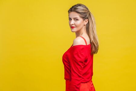Half turn portrait of gorgeous elegant young woman with neat ponytail hairstyle in red dress standing, looking at camera with serious confident face. indoor studio shot isolated on yellow background 스톡 콘텐츠