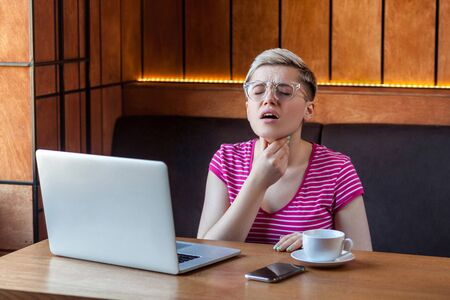 Portrait of sickness young adult woman with short blonde hair in pink t-shirt and eyeglasses sitting in cafe and touching throat with hand have a discomfort, inflammation tonsils. Indoor, health care