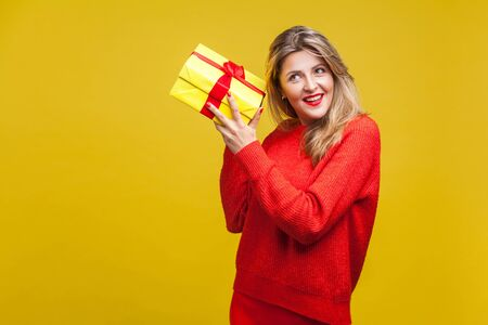 Portrait of interested beautiful blonde woman with red lipstick in casual sweater, listening to wrapped gift box, curious about birthday surprise. indoor studio shot isolated on yellow background