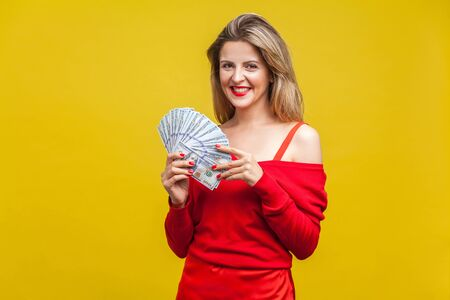 Portrait of wealthy beautiful young woman in red dress standing with dollar bills, looking at camera and smiling excitedly, enjoying rich life. indoor studio shot isolated on yellow background 스톡 콘텐츠