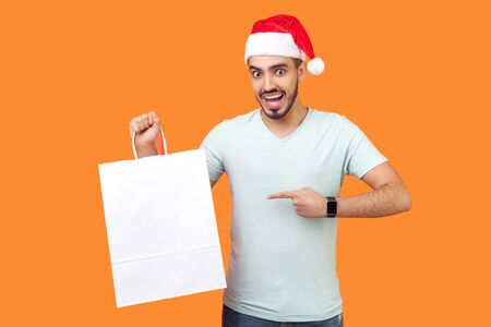 Portrait of amazed bearded young man in santa hat and casual white t-shirt standing pointing at white bag, looking surprised about xmas shopping. indoor studio shot isolated on orange background Banque d'images - 132213168
