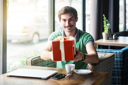 Young happy businessman in green t-shirt sitting and holding and giving big red gift box. looking at camera with toothy smile. business and freelancing concept. indoor shot near big window at daytime. Stock fotó