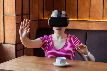 Young adult woman in pink t-shirt sitting in cafe, wearing virtual reality headset and watching video, playing game on simulator with amazed face and raised arms, looking and trying to touch. Indoor