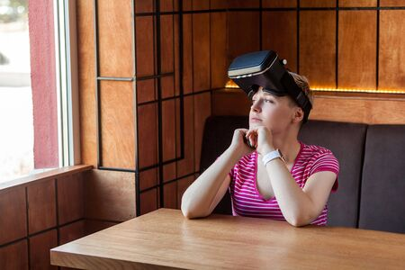 Portrait of dreaming young woman in pink t-shirt sitting in cafe, wearing virtual reality headset on the head and looking at window with thinking face. Indoor, lifestyle