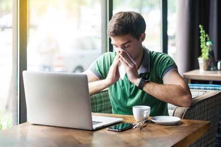 Young cold sick businessman in green t-shirt sitting at work, sneezing and cleaning his nose with tissue napkin. business and helthcare concept. indoor shot near big window at daytime. Stock Photo