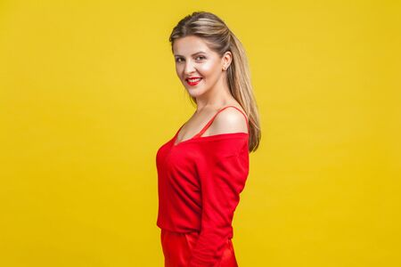 Half turn portrait of happy elegant young lady with neat ponytail hairstyle, bright makeup in red dress standing, looking at camera with toothy smile. indoor studio shot isolated on yellow background