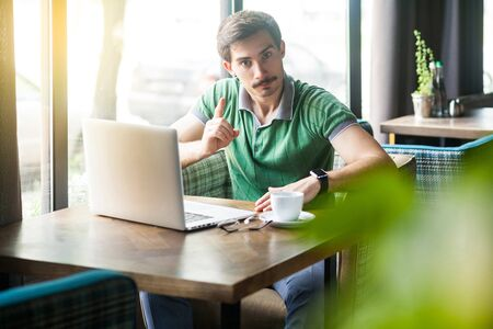 Hey you! Young serious businessman in green t-shirt sitting and working on laptop, looking at camera with warning sign. business and freelancing concept. indoor shot near big window at daytime.