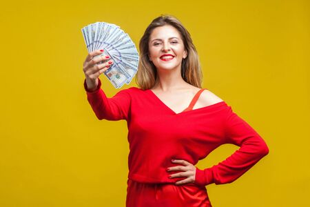 Portrait of arrogant wealthy beautiful woman in red dress standing showing dollar bills, looking at camera with smile, proud of big money, income. indoor studio shot isolated on yellow background 스톡 콘텐츠